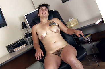 Valerie plays with her hairy pussy at her desk