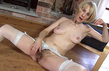 Mature minx Hazel isn\'t afraid to try new things. Today she gets all wet by blowing her skirt up with a stiff breeze and finished her self off in front of the fire place.
