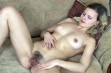 Gloria tickles her hairy pussy on the sofa