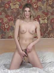 Candy Bloom strips naked on her white bed