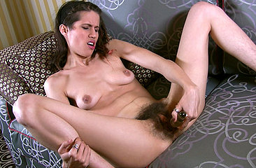Hairy diva Kitty Bush lays back on the lounge and show you her big clit as she rubs it with lube. When she is nice and moist, the sloppy sounds begin as she toys nice and deep.