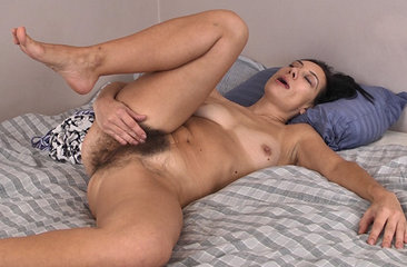 Eva is a mature brunette with a petite figure, small breasts and a hairy pussy. She gets the urge to play with herself while laying in bed in her comfortable pajamas, so she slowly strips and begins to slowly rub her clit as her hips start to move to the