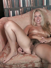 Gilian gets naked on sofa while stroking pussy