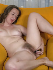 Lucia Siberia enjoys naked fun on her yellow couch