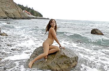 Hairy cutie Era masturbates on rocks at the beach