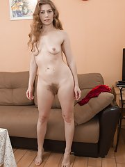 Elza strips naked on her brown couch looking sexy