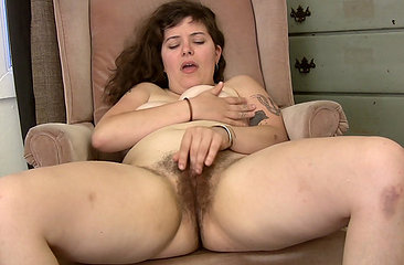 Kinky Esther puts her book down, strips from her cute lingerie and finger fucks her hairy moist pussy until she climaxes loudly on the chair.
