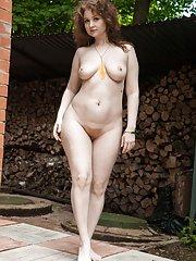 Bazhena strips naked in her outside garden